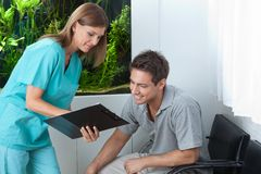 Dentist Showing Something To Patient On Clipboard. Female dentist showing something to male patient on clipboard at clinic Stock Image