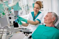 Dentist showing teeth problem on dental X-ray Royalty Free Stock Photos