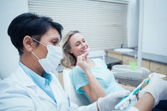Dentist showing woman how to brush teeth Stock Images