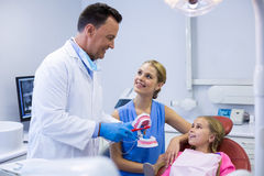 Dentist showing young patient how to brush teeth Stock Photography