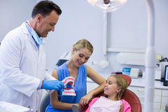 Dentist showing young patient how to brush teeth Royalty Free Stock Photos