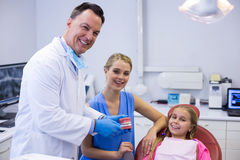 Dentist showing young patient how to brush teeth Stock Images