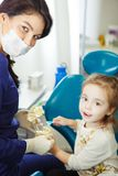 Dentist shows child how to take care of teeth. Dentist in mask and work uniform shows child how to take care of teeth with toothbrush on artificial model of Royalty Free Stock Photos