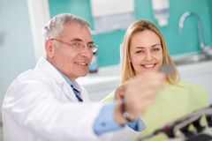 Dentist shows dental film to female patient Royalty Free Stock Photos