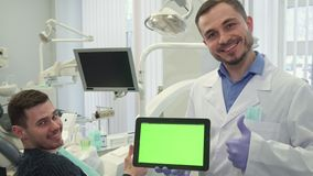 Dentist shows his thumb up at his office. Middle aged dentist showing his thumb up at his office. Attractive bearded dental specialist holding digital tablet Stock Photography