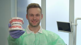 Dentist shows his thumb up. Young caucasian dentist showing his thumb up at the office. Attractive blond man in sterile gloves demonstrating layout of human stock footage