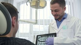 Dentist shows male client x-ray on his tablet. Middle aged male dentist showing brunette client the x-ray on his tablet. Bearded dental specialist zooming the Royalty Free Stock Photos