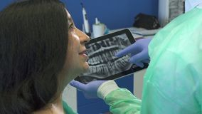 Dentist shows the patient x-ray on tablet. Close up of handsome young dentist showing female patient x-ray on tablet. Dental hygienist and senior brunette women Royalty Free Stock Image