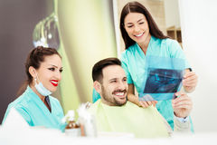 Dentist shows a patient x-ray image Royalty Free Stock Photo