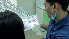 Dentist shows a patient x-ray on the tablet and