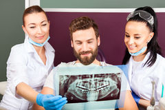 Dentist shows a patient x-ray of teeth. Royalty Free Stock Images
