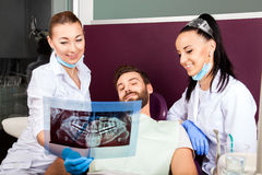 Dentist shows a patient x-ray of teeth. Royalty Free Stock Image
