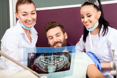 Dentist shows a patient x-ray of teeth. Royalty Free Stock Photography