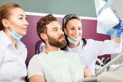 Dentist shows a patient x-ray of teeth. Royalty Free Stock Photos