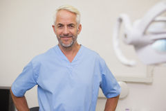 Dentist smiling at camera in blue scrubs Royalty Free Stock Photo