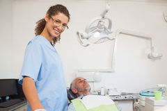 Dentist smiling at camera with patient in the chair Royalty Free Stock Images