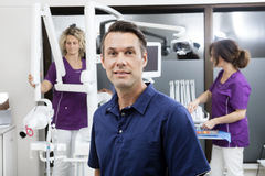 Dentist Smiling While Female Assistants Working At Clinic. Portrait of confident dentist smiling while female assistants working in background at clinic stock image