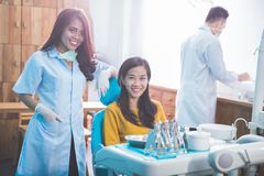 Dentist smiling with female patient in dental clinic Royalty Free Stock Images