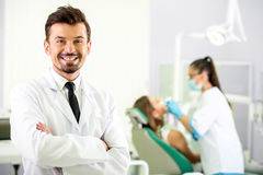 Dentist. Smiling dentist is  standing in his office. In the background a women dentist treats a patient Stock Photos