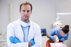 Dentist standing with arms crossed in clinic Royalty Free Stock Photos