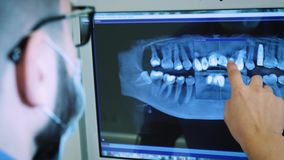 The dentist is studying the x-ray 3D image of the jaw