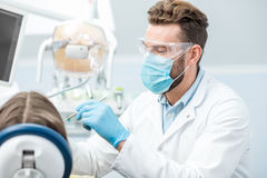 Dentist during the surgery. Portrait of a dentist in mask and protective glasses during the dental surgery Stock Photo