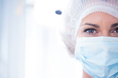 Dentist in surgical mask and cap looking at camera Stock Photography