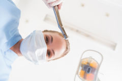 Dentist in surgical mask holding dental drill over patient Stock Photography