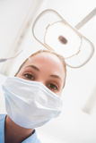 Dentist in surgical mask holding dental explorer over patient Royalty Free Stock Photo