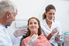 Dentist talking with patient while nurse prepares the tools Stock Images