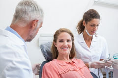 Dentist talking with patient while nurse prepares the tools Royalty Free Stock Photography