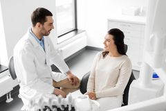 Dentist talking to female patient at dental clinic. Medicine, dentistry and healthcare concept - male dentist talking to female patient and discussing teeth Royalty Free Stock Photography