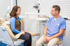 Dentist talking to patient, stomatology and health care concept stock image