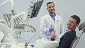 Dentist talks to his male client. Attractive male dentist talking to his handsome brunette client at his office. Caucasian bearded doctor putting medical light Stock Photos