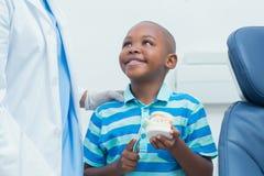 Dentist teaching boy how to brush teeth Stock Photos