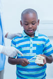 Dentist teaching boy how to brush teeth Stock Images