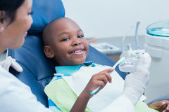 Dentist teaching happy boy how to brush teeth Stock Photos