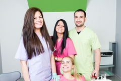 Dentist team and smiling patient. In dental office stock photography