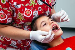 Treatment office children dentist teeth small girl teen red doctor new year discount woman clean clinic quietly comfortably Royalty Free Stock Photos