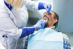 Dentist with tool cleaning teeth. Doctor with patient Stock Images