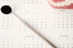 Dentist tool and demonstration teeth model on calendar Stock Images