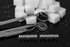 Dentist tools and mirror with sugar cubes and the words tooth decay. On beads Stock Photography