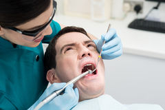 Dentist treat a man teeth Royalty Free Stock Image