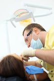 Dentist treat teeth of girl Stock Photography