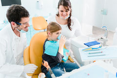Dentist treating child in his surgery Royalty Free Stock Photos