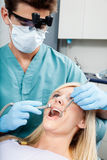 Dentist Treating A Female Patient At Clinic Royalty Free Stock Photography