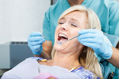 Dentist Treating A Female Patient At Clinic Royalty Free Stock Photo