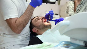 Dentist Treating A Male Patient. Assistant Helping Him stock video footage