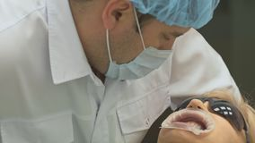 Dentist is treating patient in modern dental office. Orthodontist works with an assistant. In operation, cofferdam is. Dentist is treating a patient in a modern stock footage