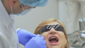 Dentist is treating patient in modern dental office. Orthodontist works with an assistant. In operation, cofferdam is. Dentist is treating a patient in a modern stock video footage